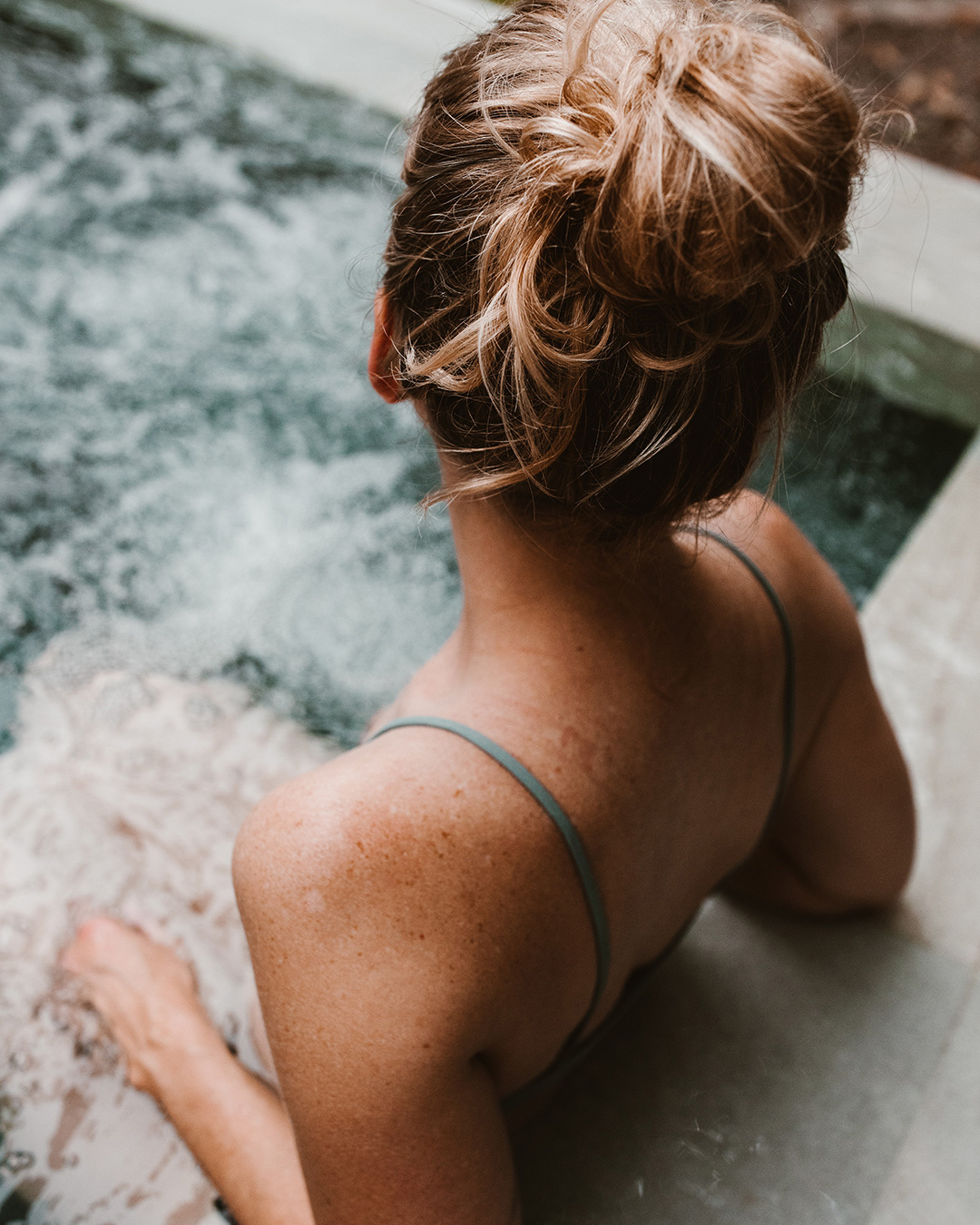 Over the shoulder shot of woman in hot tub