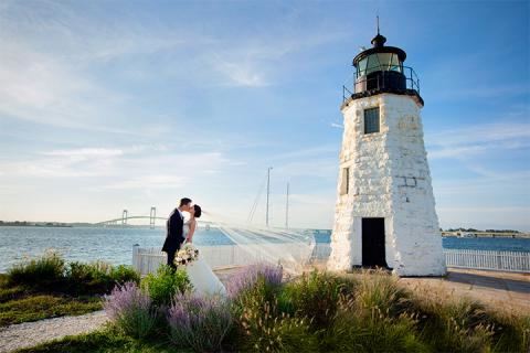 Married couple kissing by lighthouse